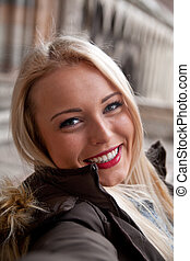 fake selfie-view of a woman taking a self portrait with her mobile and a smiling expression