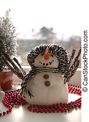 fake snowman on the sill near window