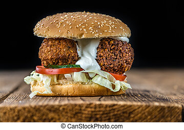 Falafel Burger (close-up shot; selective focus) on wooden ...