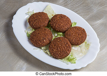 Falafel, lotus leaf filled with salad in a white dish