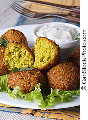 falafel on lettuce leaves with tzatziki sauce, vertical -...