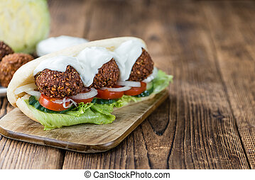 Falafel Sandwich (close-up shot) on an old wooden table