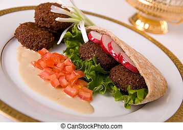 falafel in pita bread dressed on a gold lined plate with...