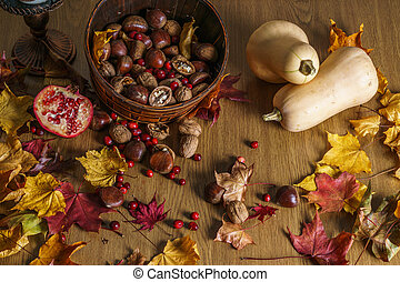 Fall autumn harvest background with pumpkin chestnut walnut on a wooden table.