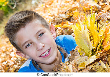 Fall. Boy teenager  with leaves in autumn park