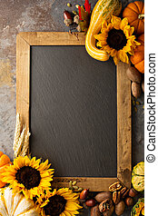 Fall chalkboard copy space with pumpkins and sunflowers