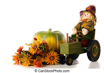 A scarecrow on a wooden tractor by a simple pumpkin and fall flower display. Isolated on white.