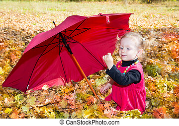 Fall. Cute child girl playing with fallen leaves in autumn park