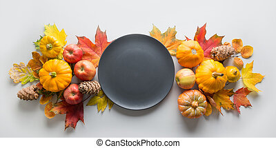 Fall decor for Thanksgiving Day with pumpkins, leaves, apples on grey.