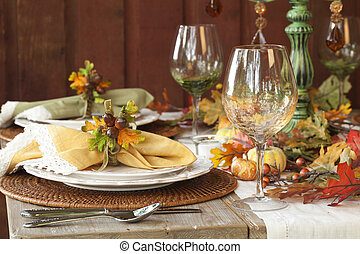 Fall dining place settings on rustic table and dark red wall