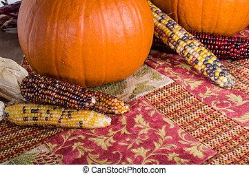 Fall display of orange pumpkins and corn
