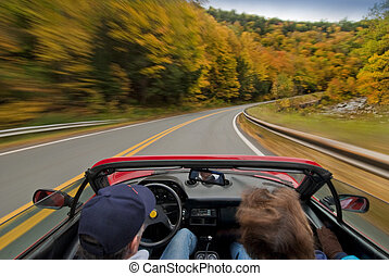 convertible driving through the new england fall season
