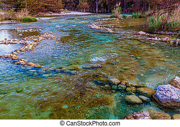 Fall foliage on the crystal clear Frio River in Texas. -...