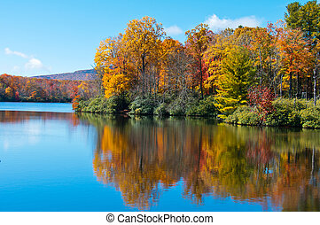 Colorful autumn foliage casts its reflection on the calm waters of the North Carolina lake.