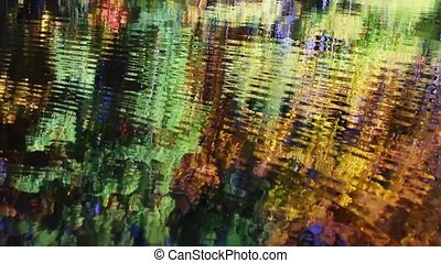 Loop with colorful fall fall foliage reflected upon the surface of a pond with gently rippling waves.