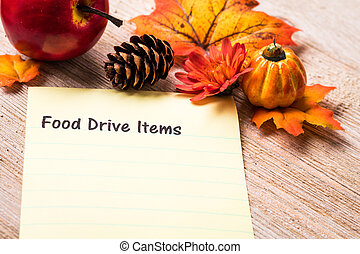 Fall Food Drive Items list concept on notebook and wooden...