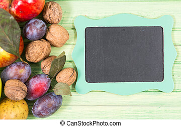 Fall fruits and small empty blackboard with copyspace