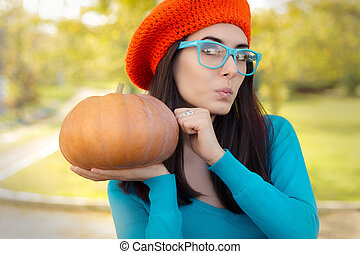 Curious autumn girl with crocheted beret, eyeglasses and pumpkin