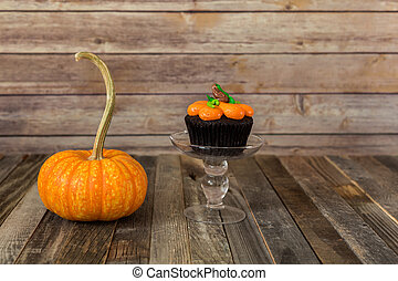 Fall gourd and pumpkin muffin on wooden backdrop