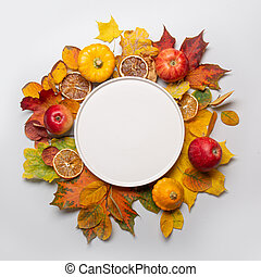 Fall harvest of apple and colorful leaves and black plate in the center with space. Top view.