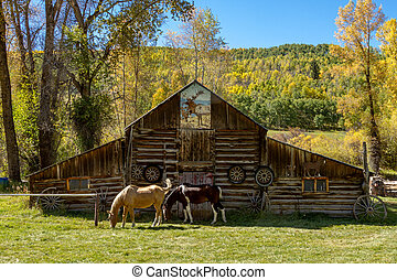 2 horses grazing in front of rustic wooden barn decorated with old western wagon wheels