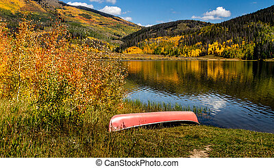 Bright red canoe sitting on shore of mountain lake on fall afternoon with brightly colored changing Aspen trees on slopes reflecting in water