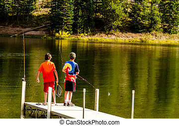 CLARK COLORADO/U.S.A - September 27, 2014: 2 young boys fishing off pier at Pearl Lake State Park on warm autumn afternoon on September 27, 2014 near Steamboat Spring, Colorado