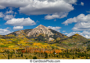Hahn Peak near Steamboat Lake State Park with changing Aspen trees on mountain slopes on sunny autumn afternoon