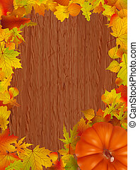 Fall leaves and pumpkins on wood background.