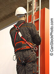 Worker on a Ladder Uses a Safety Harness to Prevent Falling From Building