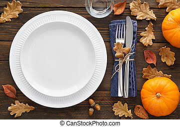 Fall season table setting with pumpkins, leaves and cutlery.
