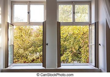 Fall season. Trees with autumn leaves out of two open white wooden windows.