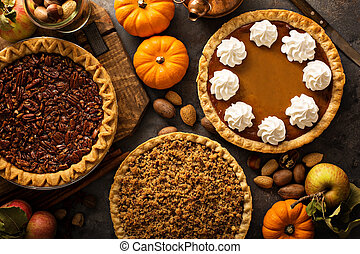 Fall traditional pies pumpkin, pecan and apple crumble pie overhead shot