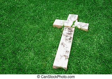 Fallen and broken down marble cross resting on a green grass