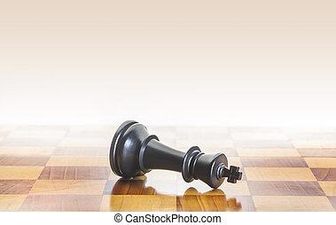 Fallen chess king as a metaphor for