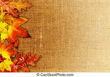 Fallen foliage over old hessian fabric, abstract autumn backgrounds