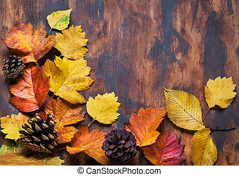 Fallen leaves on wooden background, top view, copy space