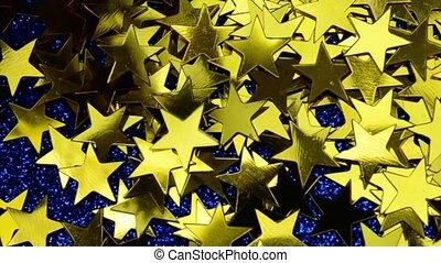 Fallen stars dark sky space. Gold yellow confetti on classic blue glitter lights close up macro background