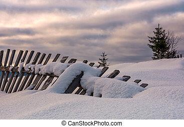 fallen wooden fence on snowy hillside. lovely rural scenery...
