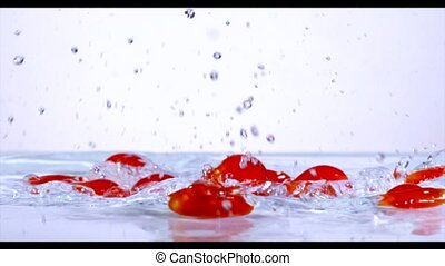 Falling and splashing cherry tomatoes on water.