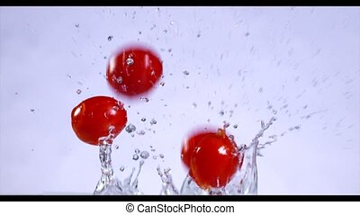 Falling and splashing cherry tomatoes on water. Slow motion.