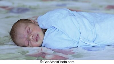 A baby swaddled in a diaper falls asleep
