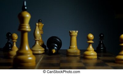 Falling black chess king on wooden board. Lose game and fail...