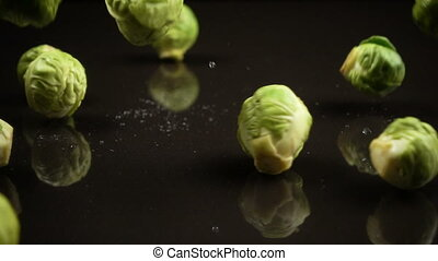 Falling brussels cabbage on black background
