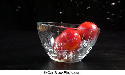Falling cherry tomatoes in glass bowl, slow motion 250 fps