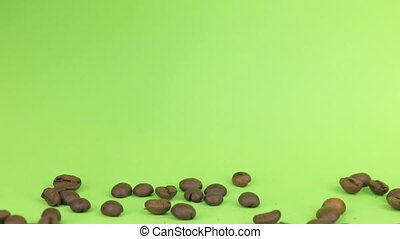 Falling coffee beans on heap of coffee beans on a green screen