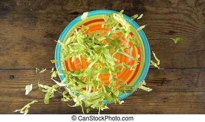 falling cut cabbage in dish with salad, slow motion
