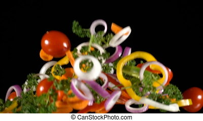 Falling cuts of plenty colorful vegetables, slow motion -...