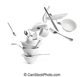 Falling dishes with cutlery on white background