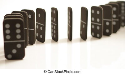 Falling dominoes coming towards you on white